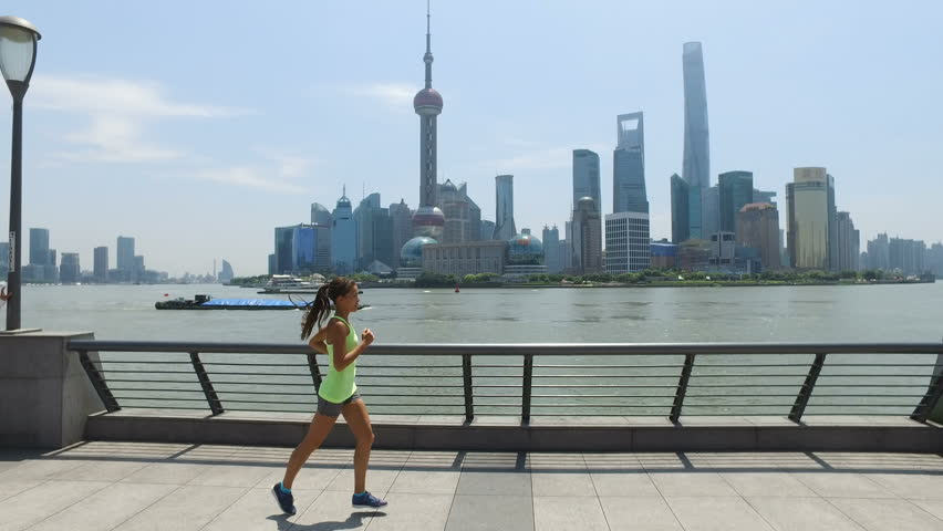 Asian woman running in city of Shanghai, China on famous boardwalk with skyline. Urban city lifestyle. Active woman runner exercising outside jogging on the Bund. Action camera