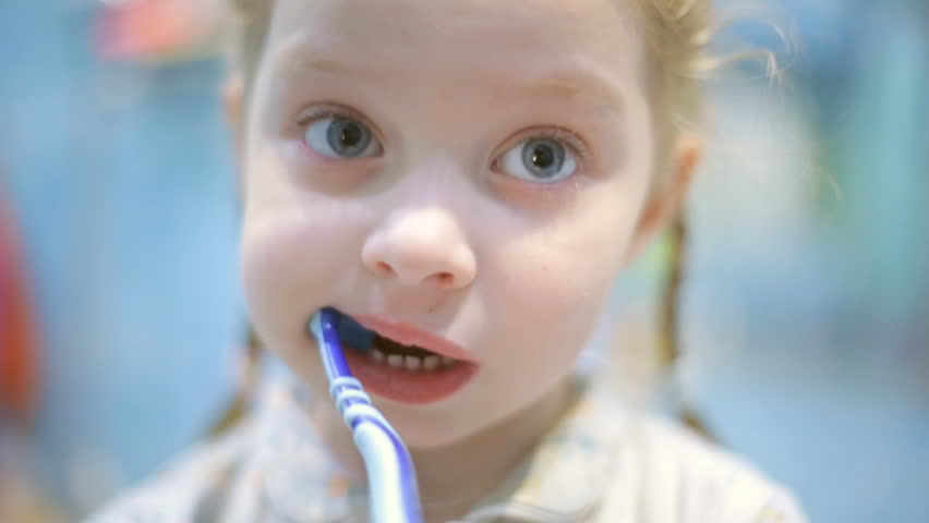Little girl f brushing her teeth with a toothbrush in bathroom in the morning   Shutterstock HD Video #1023170035