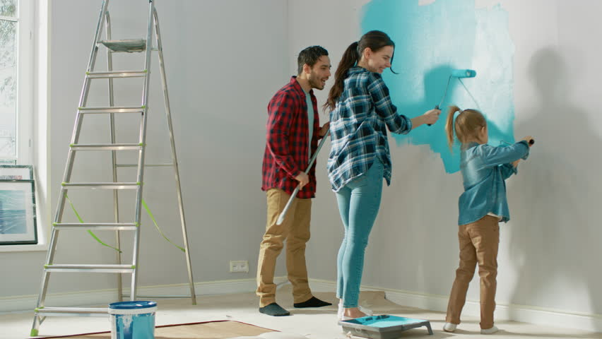 Beautiful Young Family are Showing How to Paint Walls to Their Adorable Small Daughter. They Paint with Rollers that are Covered in Light Blue Paint. Room Renovations at Home. #1023187933