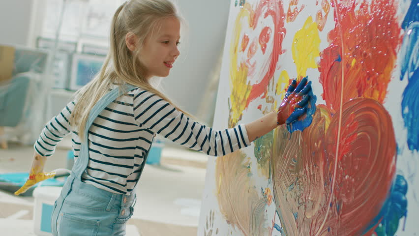 Happy Little Girl with Hands Dipped in Vivid Paint Draws Colorful Abstractions on the Wall. She is Having Fun and Laughs. Home is Being Renovated. | Shutterstock HD Video #1023188080