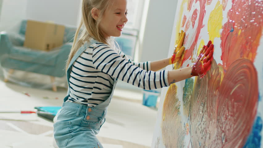 Happy Little Girl Dips Her Hands in Paint and Starts Painting Handprints on the Wall. She is Having Fun and Laughs. Home is Being Renovated. | Shutterstock HD Video #1023188089