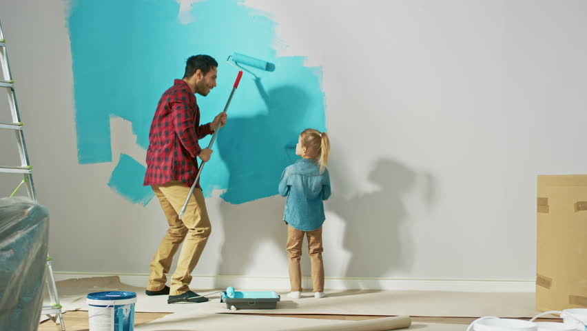 Young Father is Showing How to Paint Walls to Cute Small Daughter. They Paint with Rollers that are Covered in Light Blue Paint. Room Renovations at Home. #1023188104