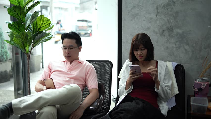 4K Locked shot with young couple sitting on chair and used smartphone in coffee shop ignoring each other, monophobia concept | Shutterstock HD Video #1023193501