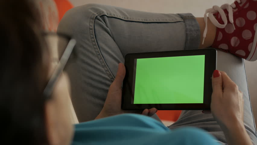 Girl using digital tablet.  Woman holding a tablet in the hands of a green screen green screen, hand of man holding mobile smart phone with chroma key green screen on white background. Technology.