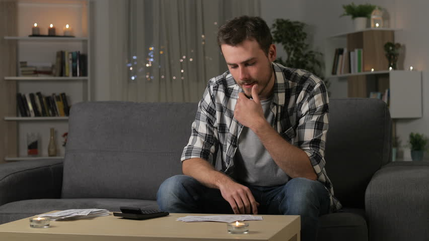 Serious man accounting checking printed receipts sitting on a couch in the night at home Royalty-Free Stock Footage #1023197899