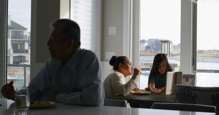 Front view of multi-generation Asian family eating food at dining table in a comfortable home. Granddaughter using digital tablet  | Shutterstock HD Video #1023204109