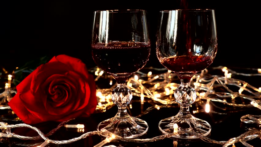 Glass with wine and a rose against the background of bright garlands. | Shutterstock HD Video #1023232111