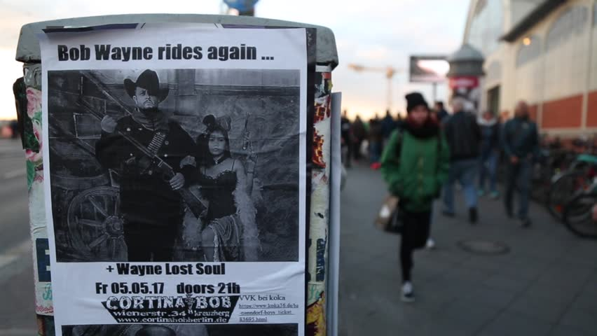 """Berlin, Germany - april.2017. In the foreground is a poster with a placard. With the inscription: """"Bob Wayne rides again""""."""