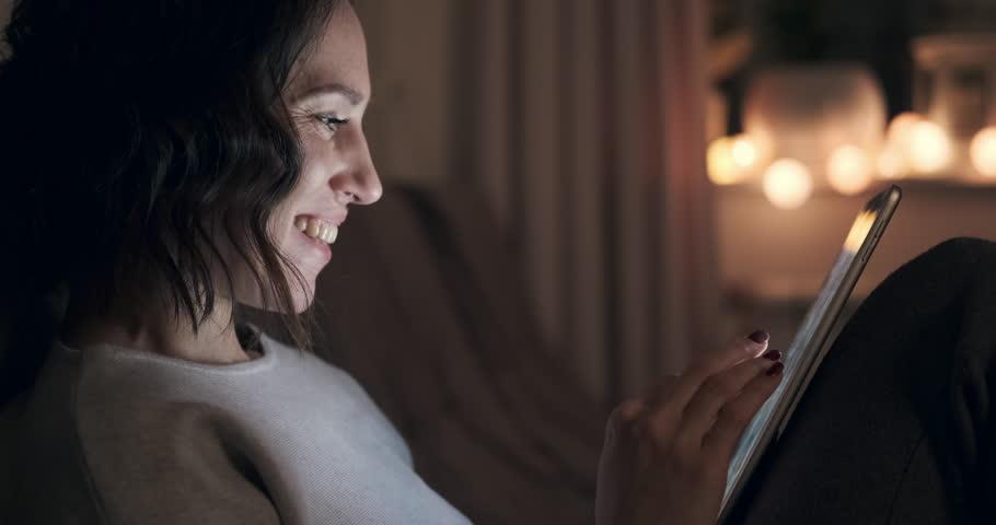 Happy woman using digital tablet at night