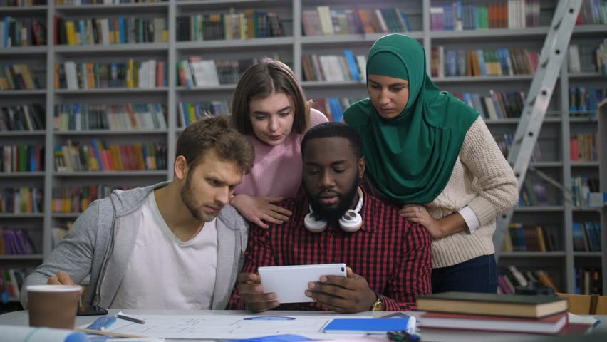 Stressed diverse multiracial college students checking failed exam online with tablet pc, expressing negativity and disappointment in university library. Worried friends desperate over bad exam result