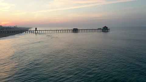 A stunning 4k parallax circling of the pier in Surf City California USA at sunrise as tourists and people on vacation enjoy the view.