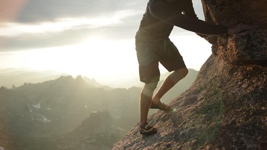 Legs of a man climbing a rock at sunset. #1023246904