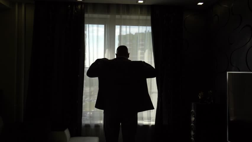 A man puts on a jacket standing in front of the window | Shutterstock HD Video #1023262117