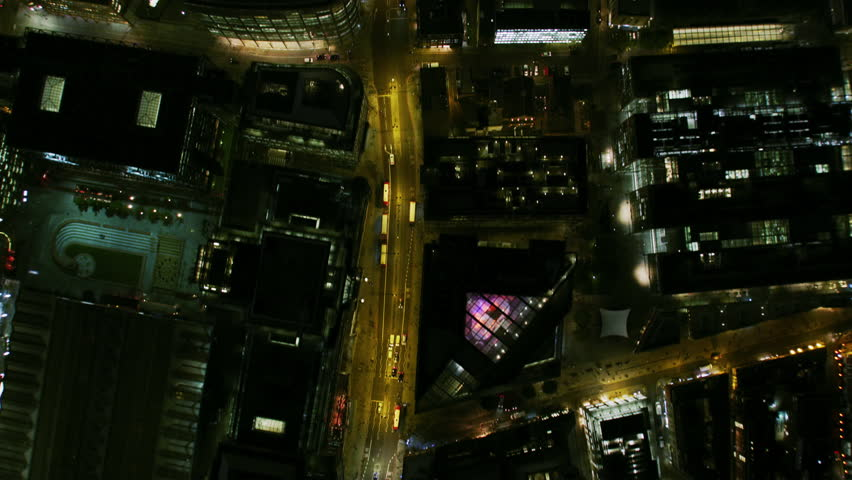 Aerial overhead rooftop view at night A10 Shoreditch illuminated streets vehicle traffic commercial buildings skyscrapers London England UK RED WEAPON