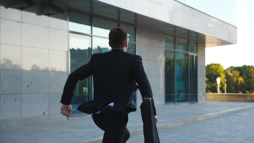 Unrecognizable businessman with briefcase runs down city street. Business man late for meeting. Successful man in suit jogging near modern building. Guy in hurry to appointment. Back view Slow motion | Shutterstock HD Video #1023267136