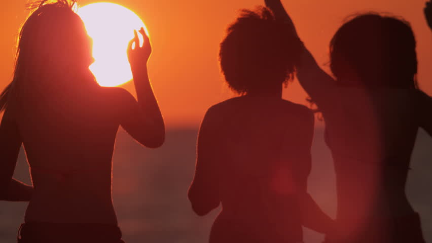 Young people in silhouette enjoying time together dancing having fun beach break at sunset shot on RED EPIC   Shutterstock HD Video #1023272101