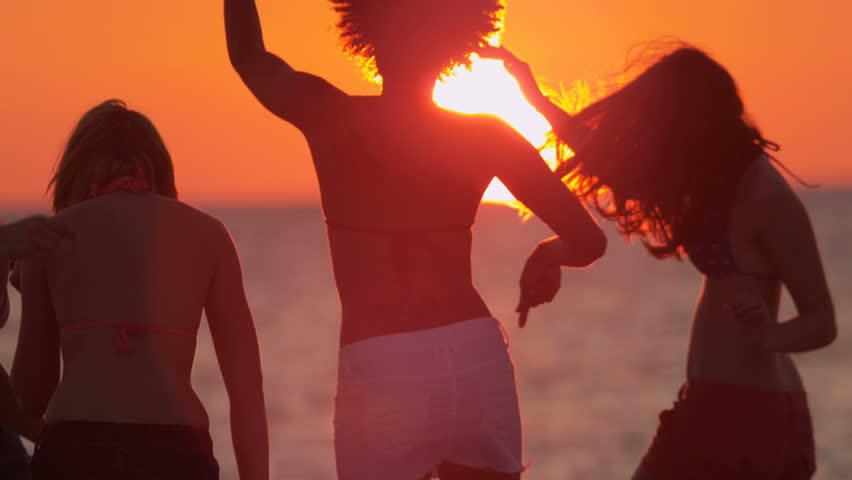 Carefree male female teenagers enjoying spring break together having fun on beach at sunset in silhouette slow motion shot on RED EPIC   Shutterstock HD Video #1023272161