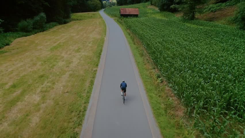 Epic aerial drone footage of professional cyclist riding down beautiful countryside road between fields and forest. Atheltic training or strength workout on sunny summer day. Healthy cycling lifestyle | Shutterstock HD Video #1023277570