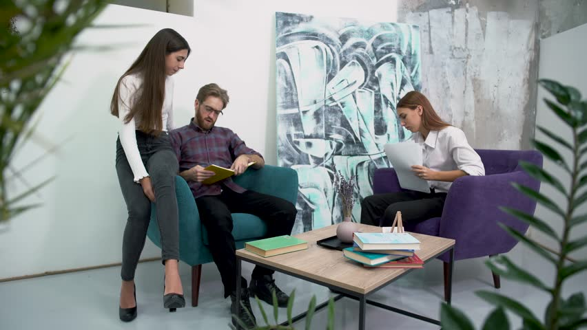 Office workers have a break sitting in comfortable armchairs and talk with each other. Discussion of work plans in a relaxed atmosphere. | Shutterstock HD Video #1023289027