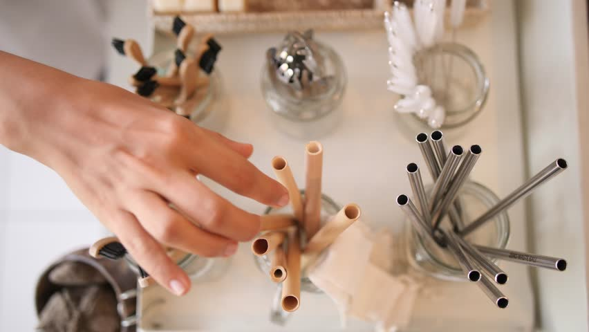 Woman Buying Bamboo Eco Friendly Biodegradable Wooden Cocktail Straw in Zero Waste Shop. No plastic Conscious Minimalism Vegan Lifestyle. Reduce Reuse Recycle 4K Slowmotion Concept.