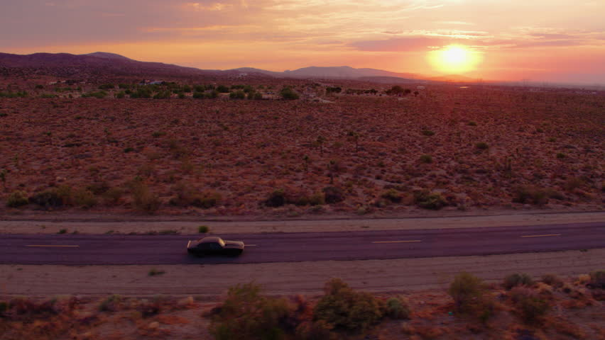 Epic sunset in desert with Classic 1969 Camaro driving down empty road - Aerial 4K | Shutterstock HD Video #1023296992