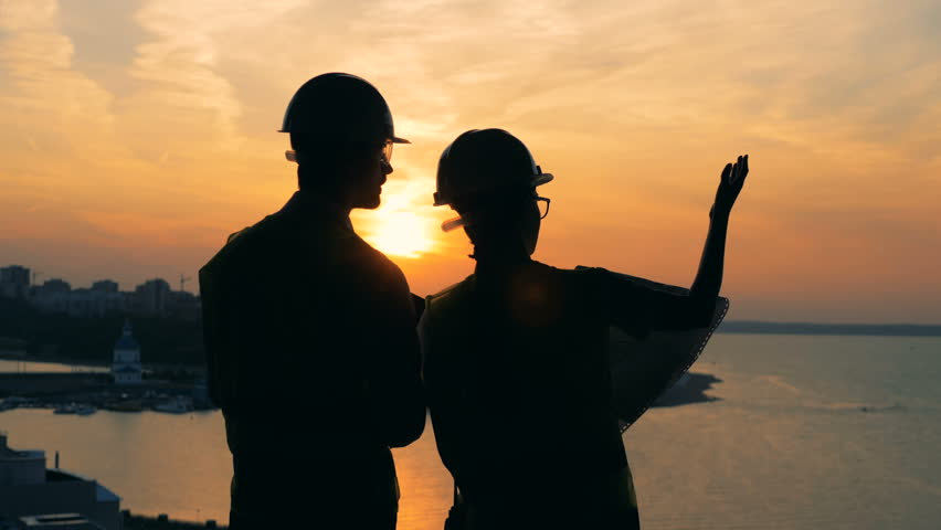 Workers talk, standing on a sunset background, back view.