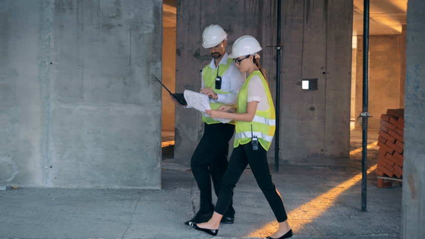 Two engineers talking while working on a construction site, side view.   Shutterstock HD Video #1023304057