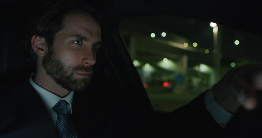 Slow motion of young handsome businessman driving a modern car in center of the city by night. Shot in 8K. Concept of business, success, traveling, luxury   Shutterstock HD Video #1023317497