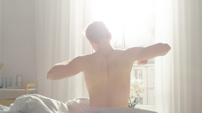 Handsome Fair Boy Sleeping Cozily in Bed, Slowly Wakes up, Gets out of Bed and Stretches Lazily. Young Caucasian Man. Early Morning Sun Shines Through the Window. | Shutterstock HD Video #1023333613