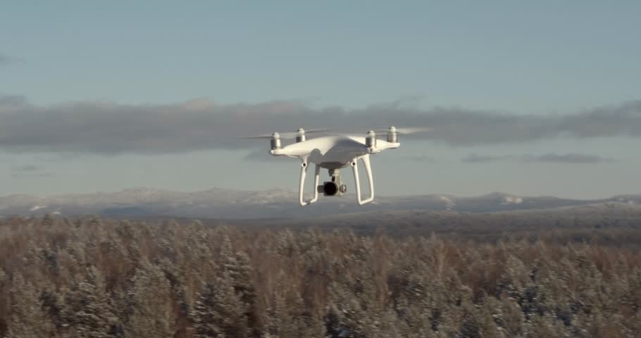 Ural Mountains, Bashkortostan / Russia - January 26 2019: Aerial View Drone DJI Phantom 4 Pro in flight from another drone over the forest mountains in winter frozen day. Reconnaissance drone.