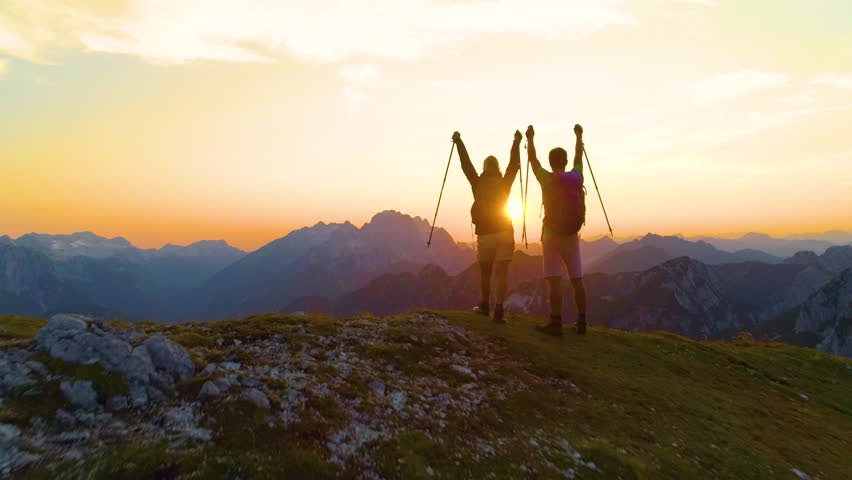 DRONE LENS FLARE: Stunning golden sunrise shines on the beautiful mountains and excited man and woman outstretching their arms. Tourist couple successfully climbs a peak in the Alps on a sunny morning | Shutterstock HD Video #1023347896