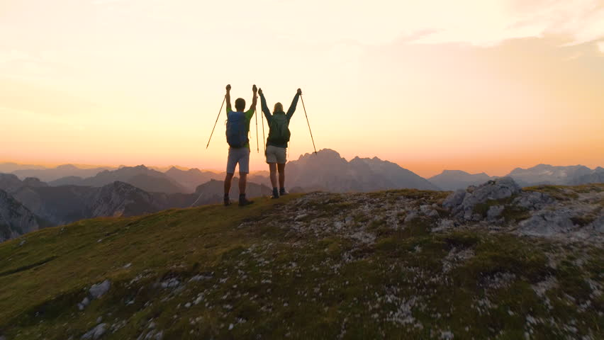 AERIAL SUN FLARE: Unrecognizable young hiker couple outstretch their arms as they catch the sunset while hiking in the Julian Alps. Picturesque shot of golden sunrise illuminating the excited couple. | Shutterstock HD Video #1023347905