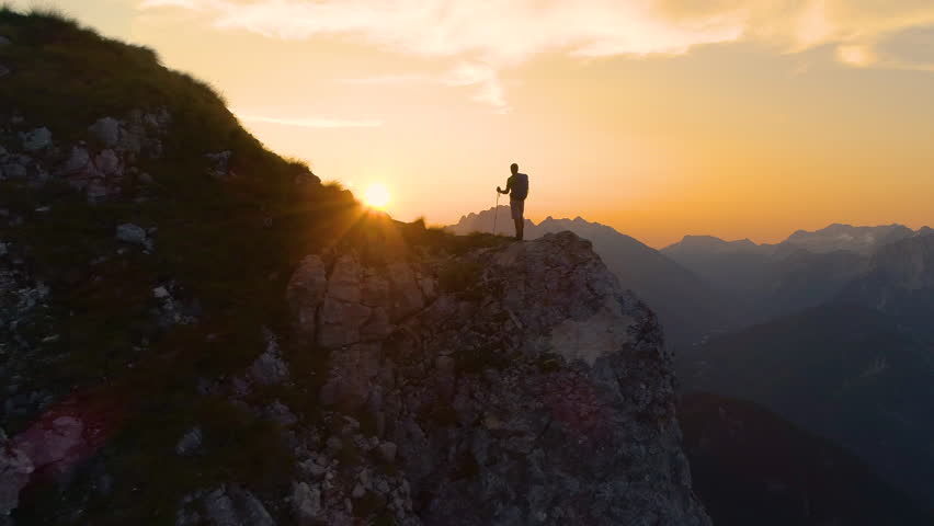AERIAL, SILHOUETTE, LENS FLARE: Stunning sunset illuminates the Alps and hiker standing on edge of a cliff and observing the picturesque mountain landscape. Man watching the sunrise in the mountains. #1023348415
