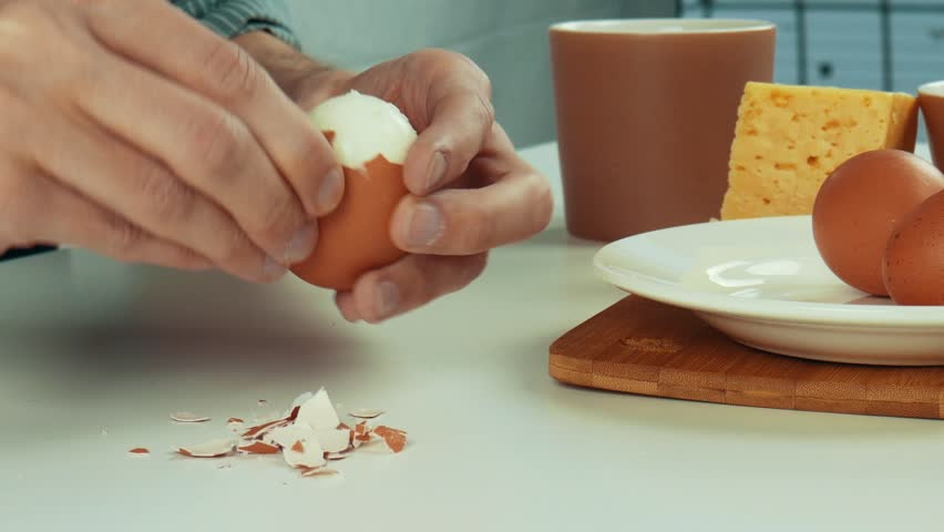 Male hands brushing a boiled egg at the dinner table. Healthy breakfast. Close up | Shutterstock HD Video #1023350257