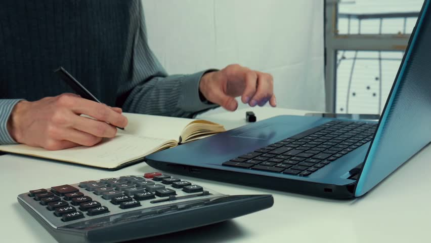 A man looks into a laptop and takes notes in his notebook | Shutterstock HD Video #1023350269