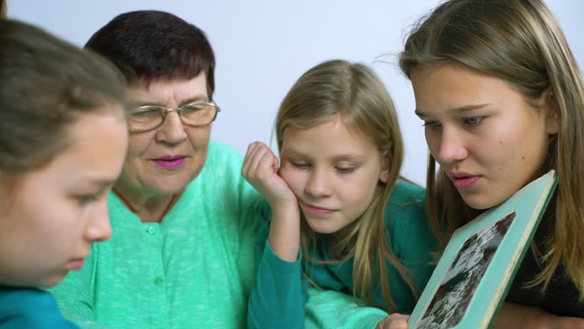 Grandmother showing old photo album to her four granddaughters #1023353113