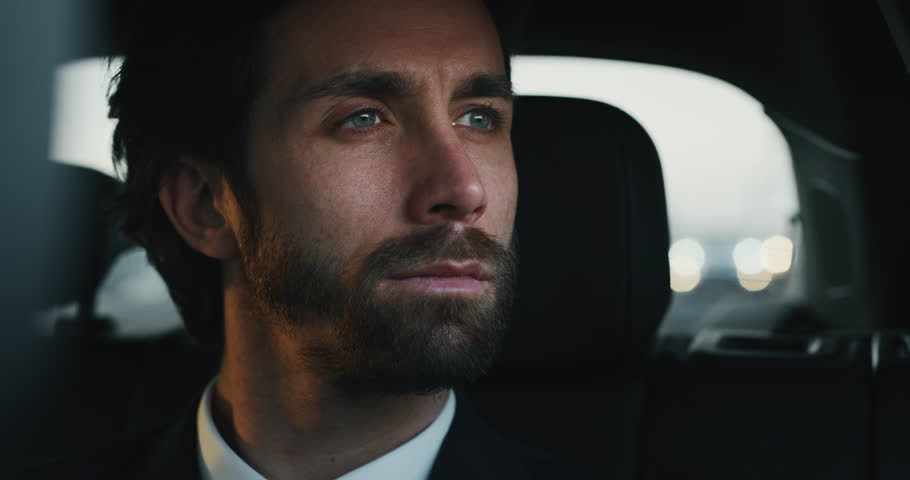 Slow motion close up of young handsome businessman looking outside during traveling in a modern car with a driver in center of the city by day.Shot in 8K.Concept of business,success, traveling luxury  Royalty-Free Stock Footage #1023373558