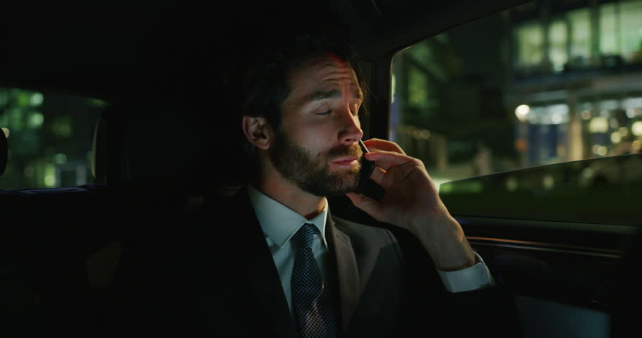 Slow motion of handsome businessman calling with mobile phone during  traveling in a modern car with a driver in center of the city by night.Shot in 8K.Concept of business, success, traveling, luxury    Shutterstock HD Video #1023373681