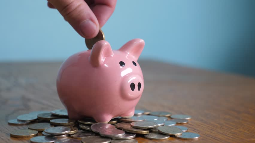 Piggy bank business standing on a pile of coins concept. A hand is putting a coin in a lifestyle piggy bank on a yellow background. saving money is an investment for the future. Banking investment and | Shutterstock HD Video #1023393748