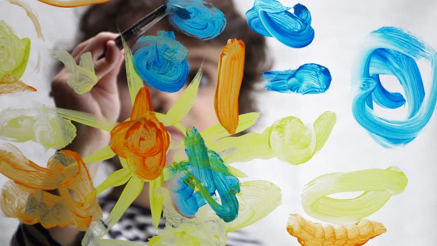Child painting with acrylic paint on transparent glass. 4K