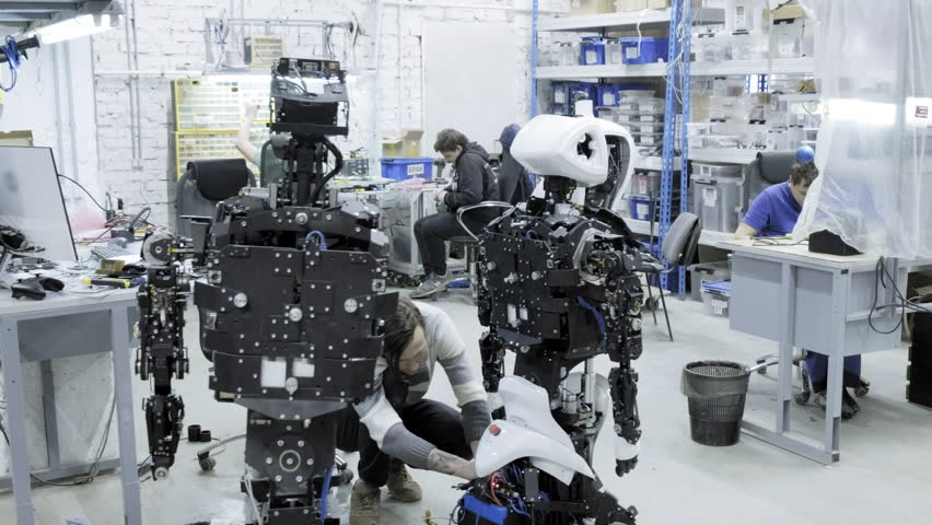 Factory for the production of robots, modern robotic developments. A group of young engineers creates new modern robots. Robots are disassembled in the shop. Royalty-Free Stock Footage #1023400099