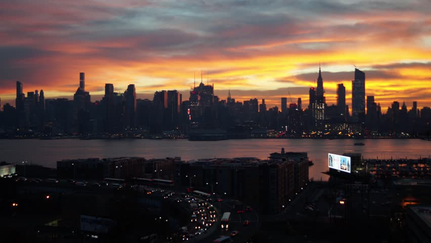 Sunrise time-lapse video of rush hour traffic and the New York city skyline.   this video shows the Manhattan skyline and the sun rising behind clouds as cars commute to the city.