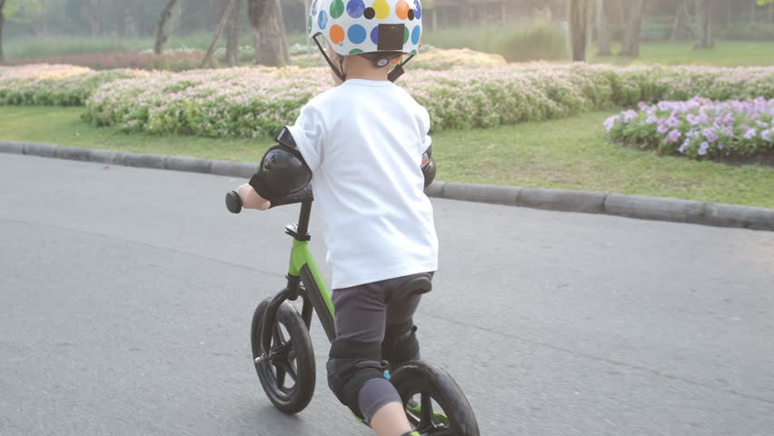 Cute little Asian 2 - 3 years old toddler baby boy child wearing safety helmet learning to ride first balance bike in sunny summer day, kid playing & cycling at park, Cycling with young kids concept