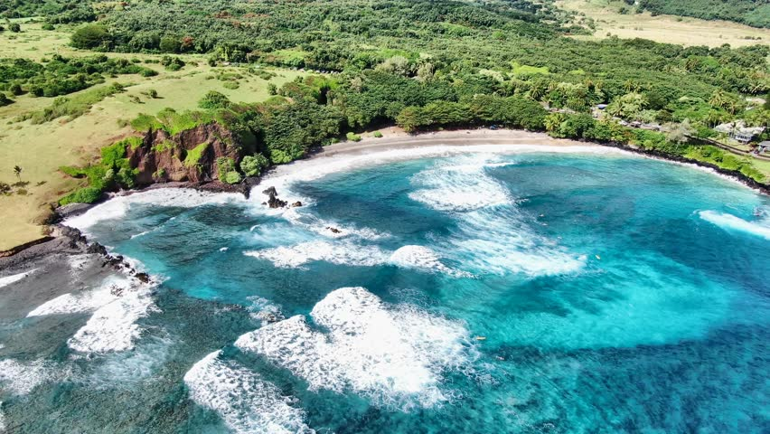 Stunning aerial drone footage of Hamoa Beach, a remote beach near the little town of Hana on the east side of the island of Maui, Hawaii. Hamoa Beach is consistently named one of Maui's Best Beaches. | Shutterstock HD Video #1023418366