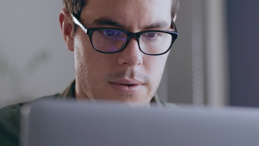 Close up of a young, caucasian businessman working on his laptop in a modern office | Shutterstock HD Video #1023427498