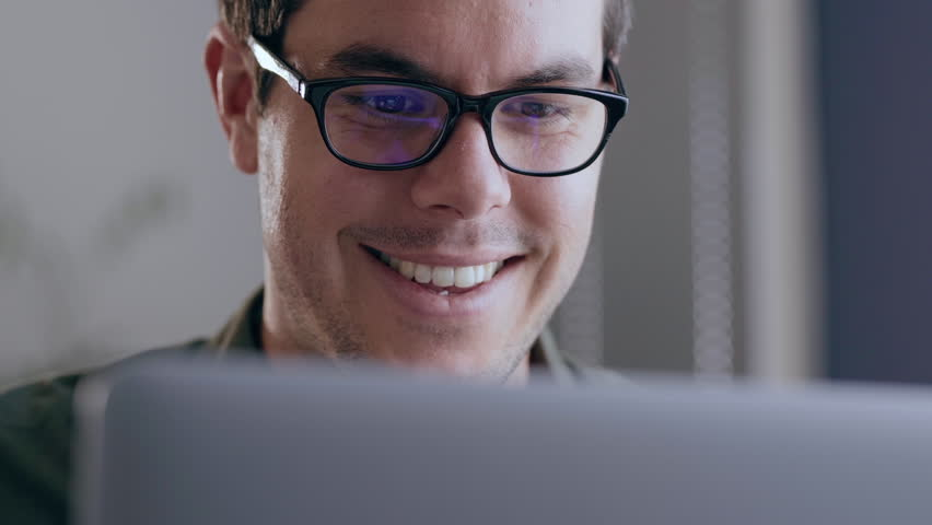 Close up of a young, caucasian businessman happily working on his laptop in a modern office | Shutterstock HD Video #1023427501