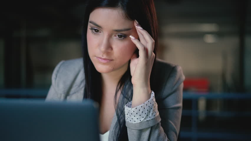 Portrait of a stressed, young brunette business woman holding her face whilst looking at her laptop in a modern office   Shutterstock HD Video #1023427579