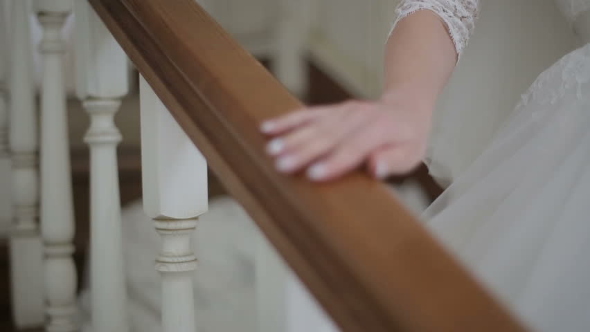 Close up of Beautiful Bride walking down stairs. Woman in white dress comes down the stairs. Slow motion