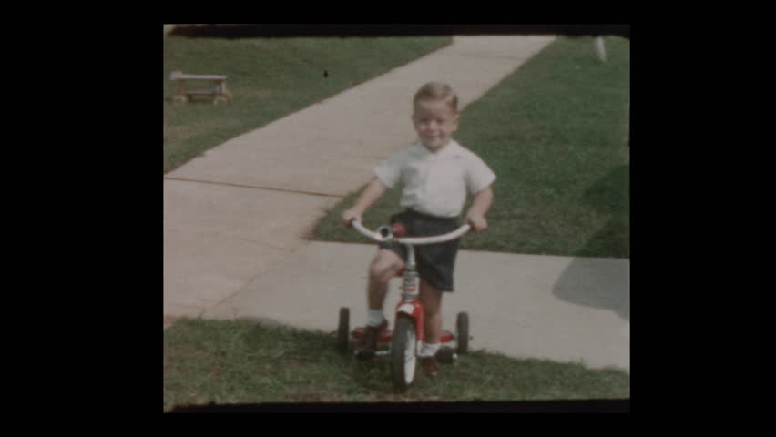 1956 Cute blond boy rides Red tricycle rides up to grandparents and mother