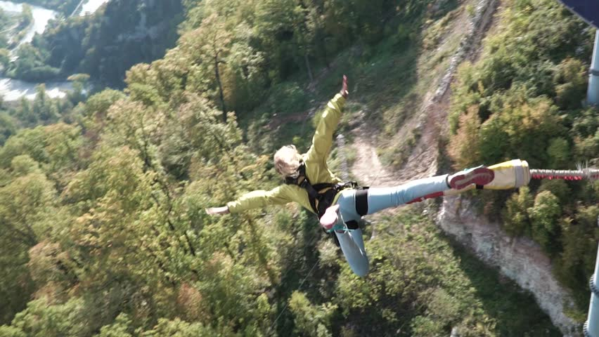 Girl has an amazing time bungee jumping in Sky Park/ Exploring extreme entertainments. Bungee in the canyon. Walking in the Skypark Sochi.